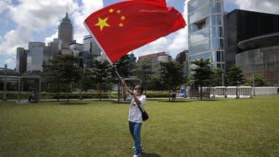 Ein Pro-China-Aktivist bejubelt mit der Staatsflagge das neue Sicherheitsgesetz für Hongkong. Die Börsen jubeln mit. (Kin Cheung / AP)