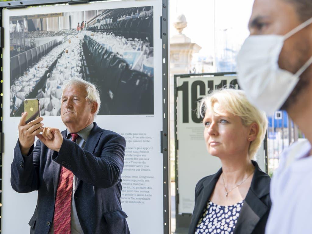 Hans Stöckli (l.) und Isabelle Moret (Mitte) besuchen eine Fotoausstellung über die Nahrungsmittelverteilung an Bedürftige während der Corona-Krise in Genf.