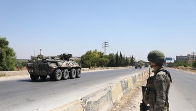 epa08520481 A soldier watches on as a tank of the Russian-Turkish joint Military patrols No. 19 drive on the M4 road linking Tranbah village to the Town of Jisr Al-Shughour, in The outskirts of Ariha south of Idlib, Syria, 01 July 2020.  The EU and the UN co-chaired, on 30 June,  the fourth Brussels Conference to seek a political solution to the Syria conflict, raise financial support for Syria and the countries in the region that host Syrian refugees.  EPA/YAHYA NEMAH (Yahya Nemah / EPA)
