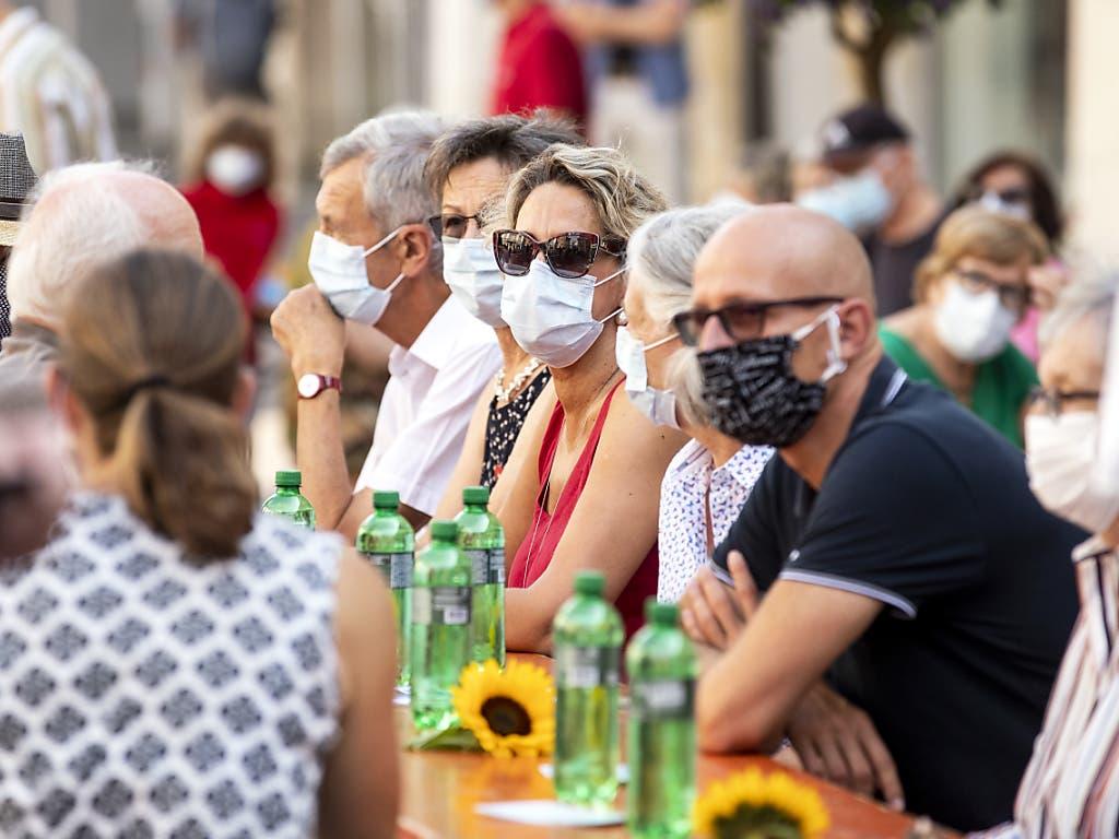 Zuhören mit Maske: Besucher der 1. August-Feierlichkeiten vom Samstagmorgen in Schaffhausen. (KEYSTONE/Alexandra Wey) Geo-Information: Schweiz/Schaffhausen Quelle: KEYSTONE Fotograf: ALEXANDRA WEY