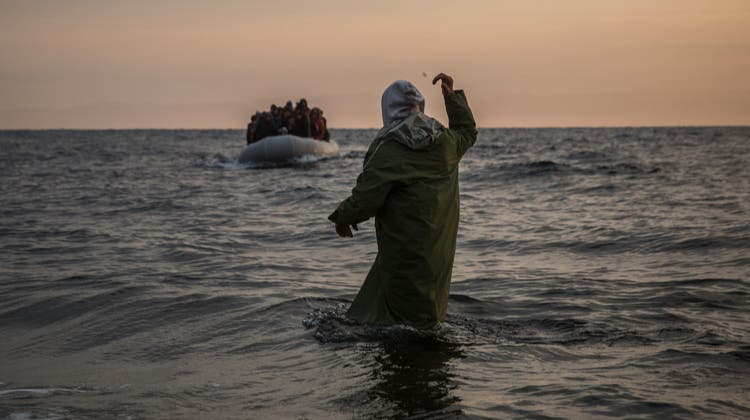 Ein Helfer winkt Neuankömmlingen auf einem Flüchtlingsboot an der griechischen Küste zu. (Keystone)