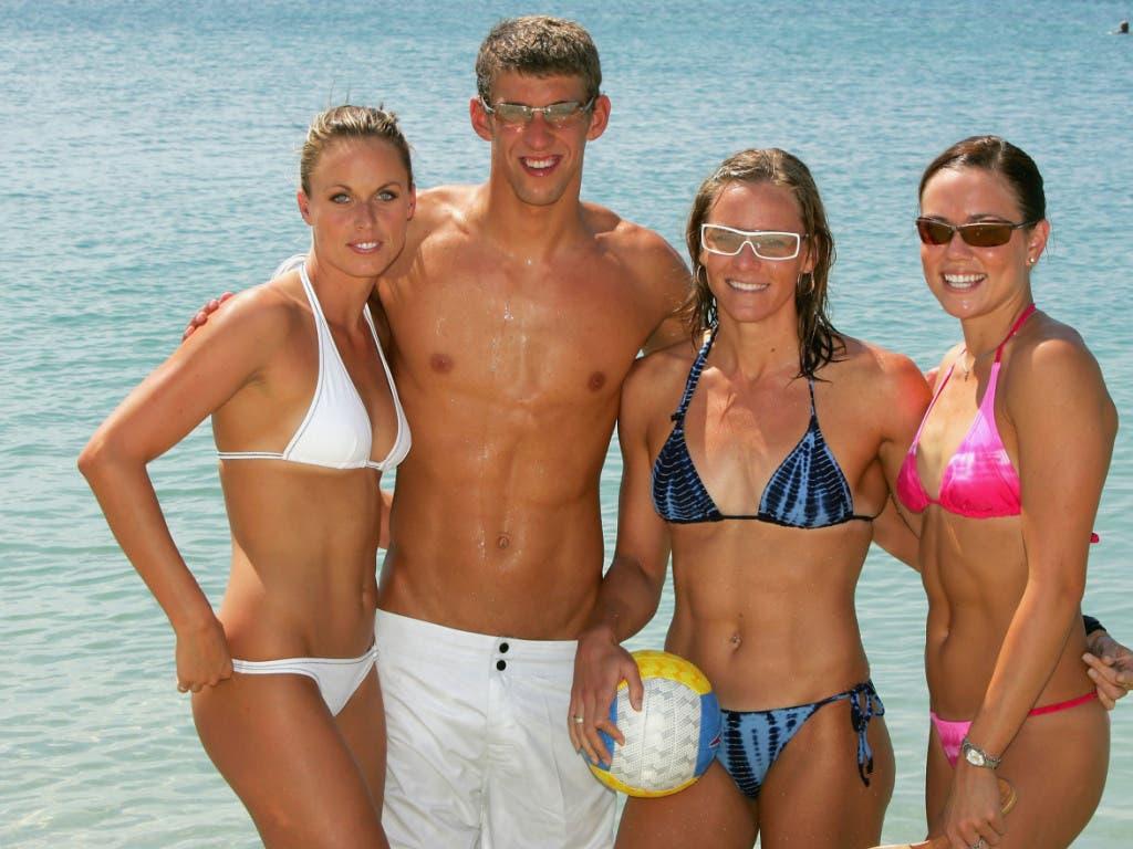 Michael Phelps 2004 am Strand von Athen mit seinen amerikanischen Teamkolleginnen Amanda Beard, Jenny Thompson und Natalie Coughlin (von links nach rechts)
