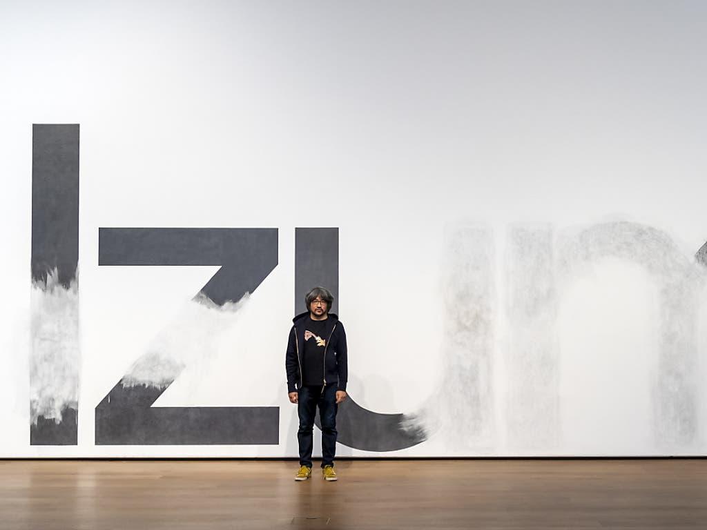 Taro Izumi vor seiner von ihm und seinem Team bearbeiteten Ankündigungswand im Museum Tinguely Basel.