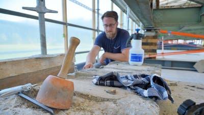 Restaurator Linus Wettstein flickt ein abgebrochenes Stück Stein mit Mörtel. Über ihm wartet die aufgebockte Stahlkonstruktion der Brücke darauf, entrostet zu werden. (Bild: Mario Testa (Bonau, 29. Juli 2020))