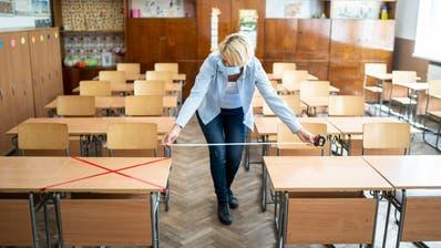 Ist der Abstand gross genug? Eine Lehrerin misst ein Schulzimmer aus. (Bild: Getty)