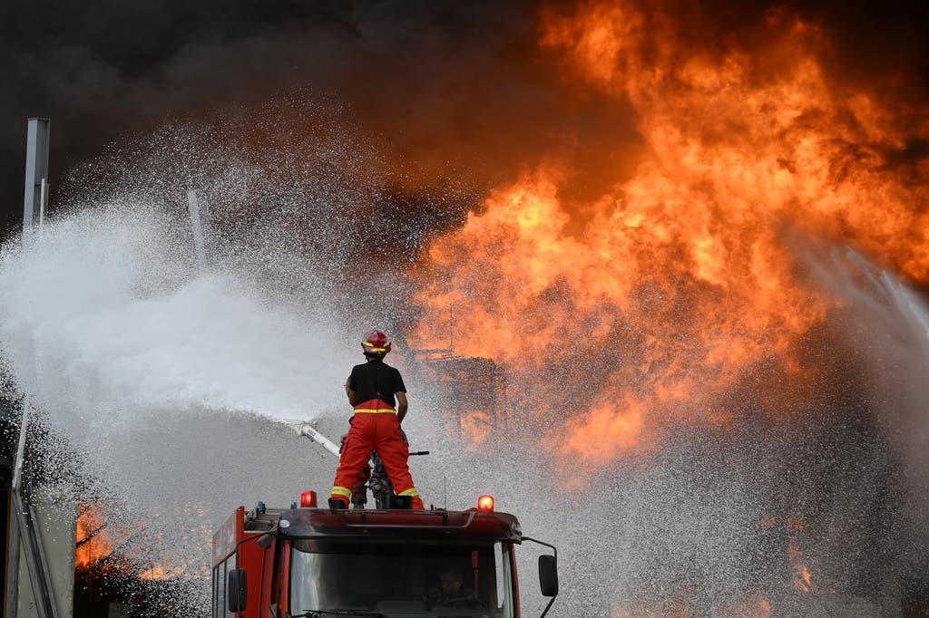 Ein Feuerwehrmann bekämpft die Flammen vom Dach eines Tanklöschfahrzeugs.