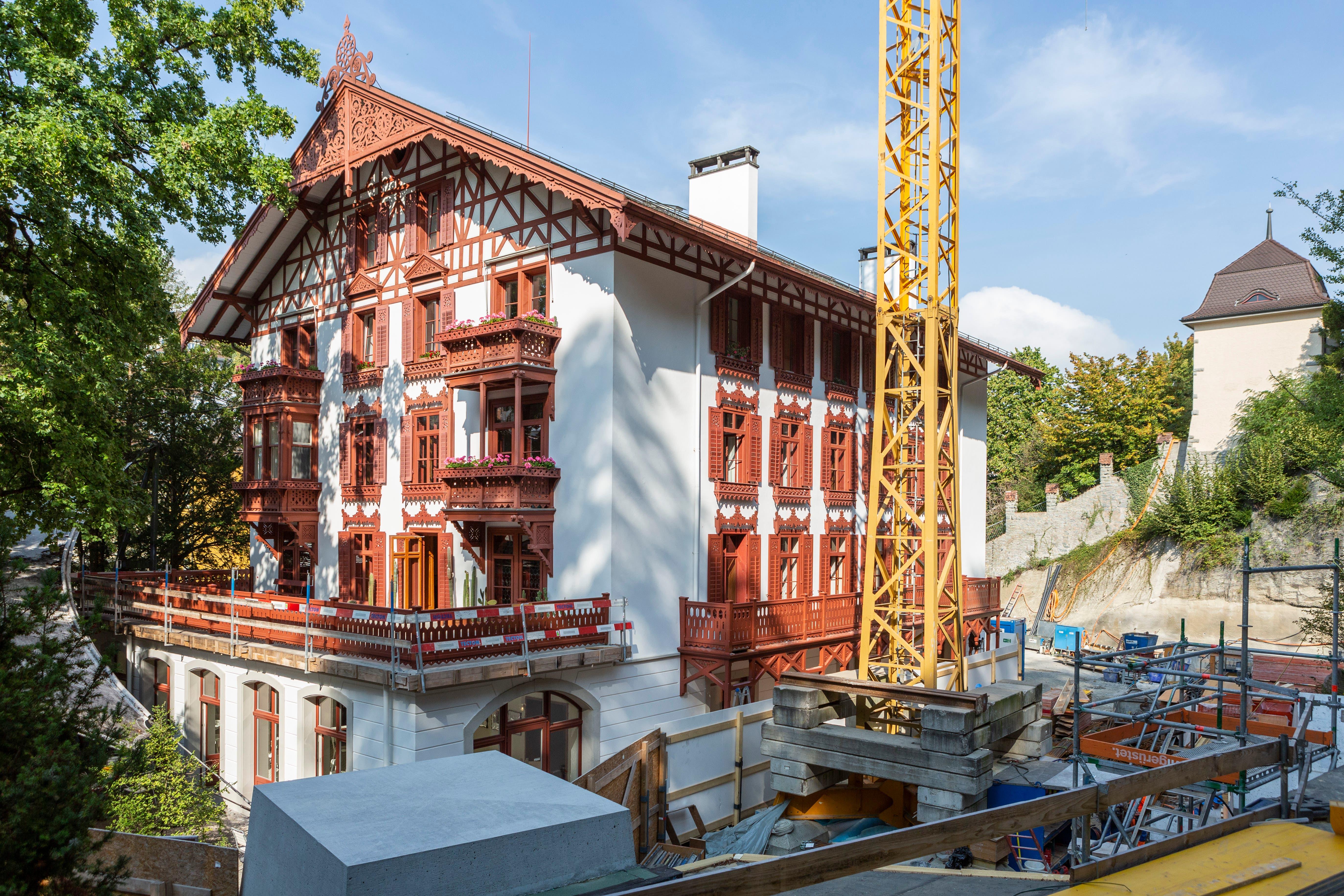 Das historische Schweizerhaus erstrahlt nach der aufwendigen Restauration in altem Glanz. Rechts daneben ist der Kran für die Arbeiten beim grossen Ausbauprojekt «Fels» des Gletschergartens.