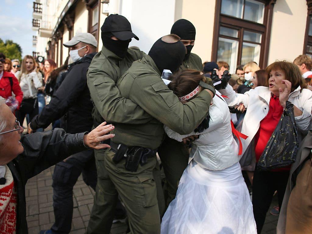 Polizisten nehmen eine Demonstrantin fest. (Bild: -/Tut.by/AP/dpa)