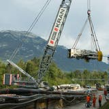 Das Maschinenrohr, mit 127 Tonnen das schwerste Teil der Tunnelbohrmaschine für den Hochwasserentlastungsstollen wird mit einem der grössten Krane der Schweiz (Fanger) in die Baugrube auf der Baustelle Alpnach gehoben. (Philipp Unterschütz / Obwaldner Zeitung)