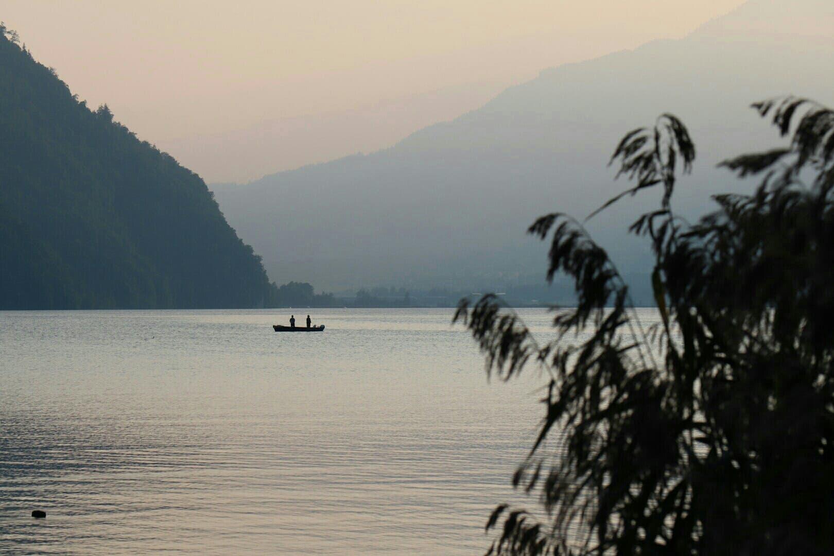 Ein einsames Fischerboot nach dem Sonnenuntergang auf dem Alpnachersee.