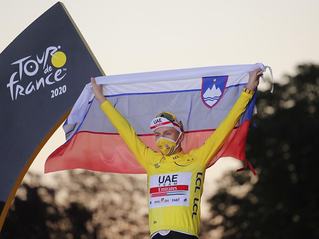 Tadej Pogacar mit der slowenischen Flagge auf dem Siegerpodest
