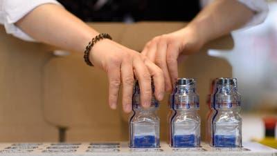 Eine Berlinger-Angestellte konfektioniert Fläschchen für Dopingproben. (Bild: Gian Ehrenzeller/Keystone (Ganterschwil, 28. Februar 2017))