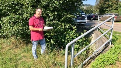 Der zuständige Gemeinderat Andreas Schär zeigt den heutigen Durchlass bei der Hauptstrasse, der vergrössert werden soll. (Bild: Samuel Koch)