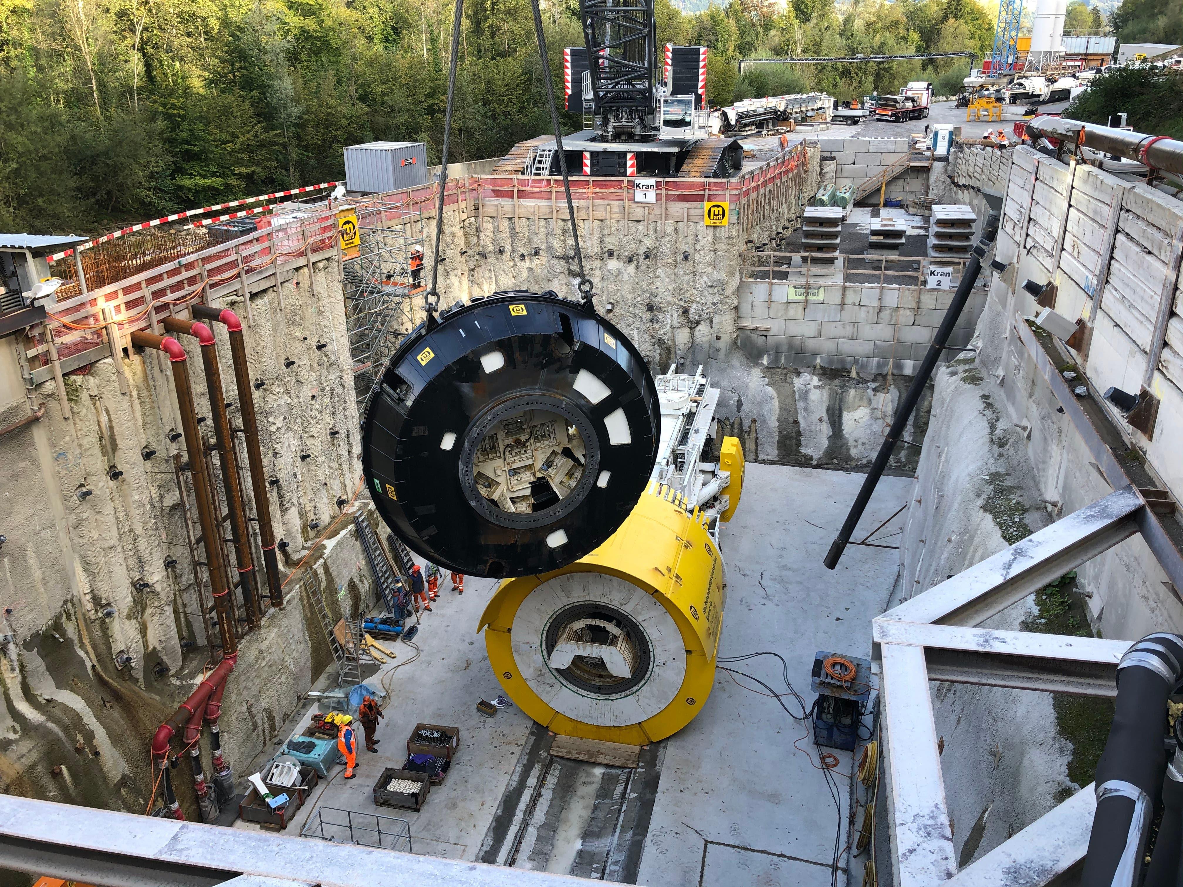 Der Bohrkopf mit einem Gewicht von 88 Tonnen und einem Durchmesser von 6,53 Metern wird in Alpnahc in die Baugrube gehievt.