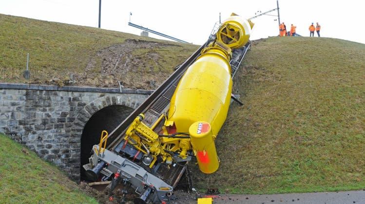 Gleisbau-Bagger donnert in Flachwagen mit Betonmischern