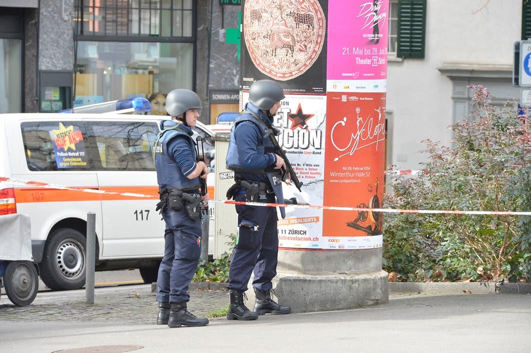 Zwei mit Maschinenpistolen bewaffnete Polizisten beobachten das Geschehen.