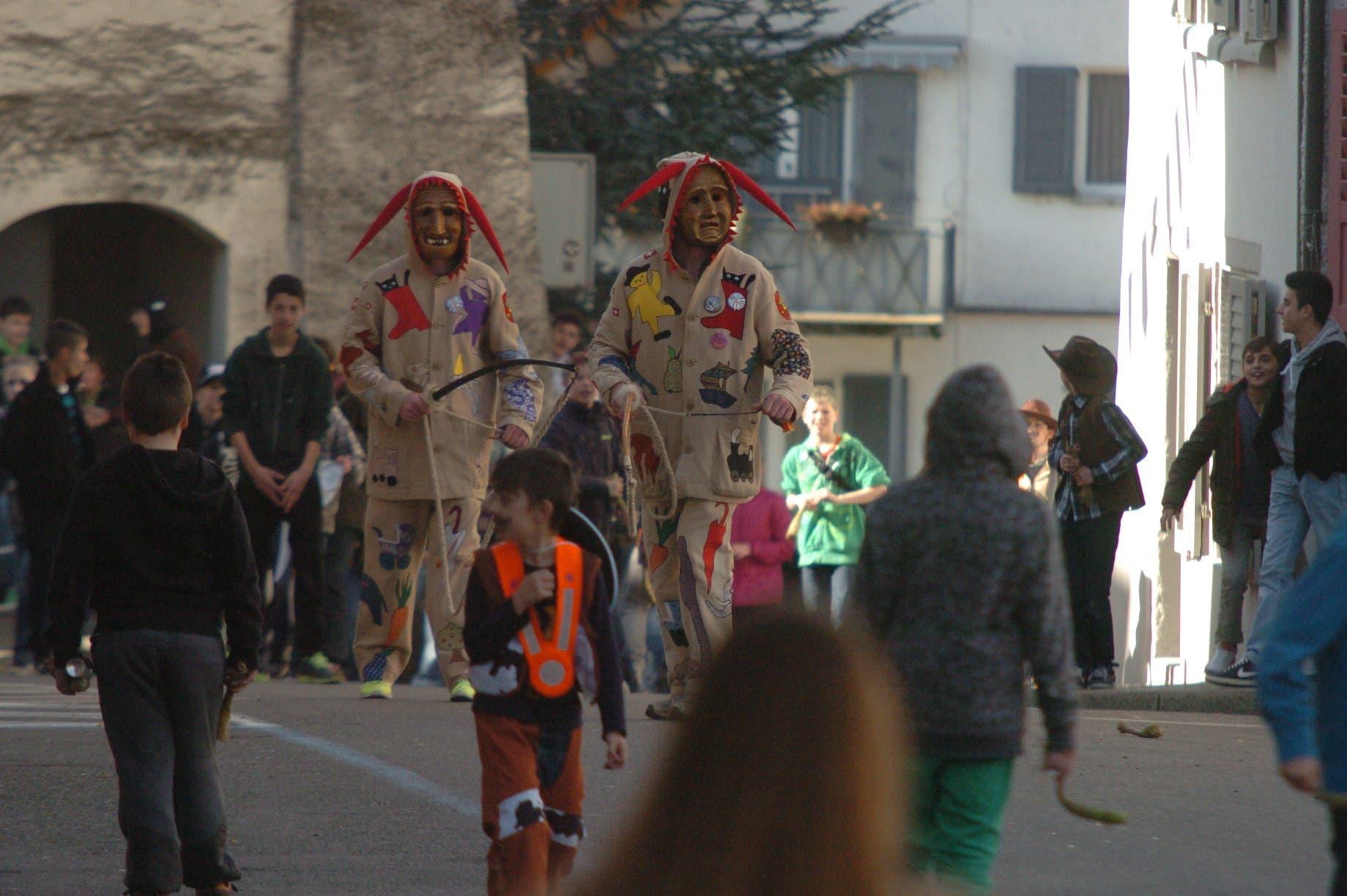 Die beiden Räbehegel im Einsatz: Mit Geisseln jagen sie die Kinder, welche die Räbehegel von hinten mit Chabisstorzen bewerfen dürfen.