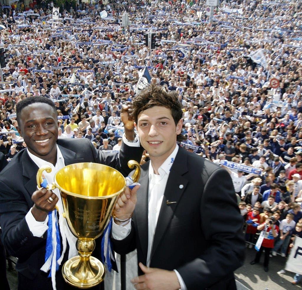 Blerim Dzemaili (rechts) und Alhassane Keita halten den Meisterpokal vor Tausenden FCZ-Fans auf dem Zürcher Helvetiaplatz.
