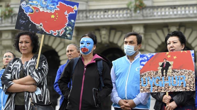 Personen mit Uiguren-Masken posieren auf dem Bundesplatz während der Einreichung der Petition #NoComplicity. (Keystone)