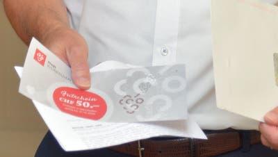 Stadtpräsident Max Vögeli zeigt die 50-Franken-Gutscheine, welche die Stadt Weinfelden allen Einwohnern zugeschickt haben. (Bild: Mario Testa (Weinfelden, 13. August 2020))