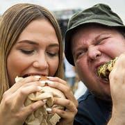 Miranda Diggelmann und Mathias Frei beissen herzhaft in Burger und Corn-Dog. (Bilder: Reto Martin)