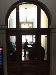 Bundesanwalt Michael Lauber (stehend, Mitte) gestern vor Zimmer 3 im Parlamentsgebäude. Abgeschirmt durch Personenschützer, die mit dem Rücken zur Glaswand stehen. (Bild: CH Media)