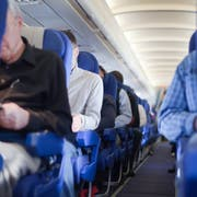 Aisle between the seats in the airplane cabin, shallow depth of focus. People out of focus.