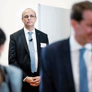 Nach getaner Arbeit tritt der Zuger Landschreiber Tobias Moser in den Hintergrund, während sich Nationalrat Thomas Aeschi (SVP, rechts) über seinen erneuten Wahlsieg freut. (Bild: Stefan Kaiser, Zug, 20. Oktober 2019)