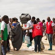 Mitarbeiter des Roten Kreuzes versorgen Menschen, die der tropische Wirbelsturm «Idai» in Moçambique obdachlos gemacht hat, mit Hilfsgütern. Bild: Denis Onyodi/EPA (21. März 2019)