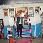 Beat Breu posiert vor seinem Bistrowagen. Neben ihm Dutzende Fotoalben zu seinem Leben, frei zugänglich für Besucher. (Bild: Livia Grob)