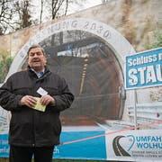 Peter Bigler (FDP), Gemeindepräsident von Wolhusen, vor dem Plakat des geplanten des Tunnels. (Bild: Boris Bürgisser, 28. November 2017)