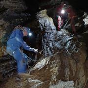 Mit Stirnlampen ausgerüstete Teilnehmer einer begleiteten Tour überwinden eine steile Passage in der Schrattenhöhle. (Bild: NeKO-Stiftung)