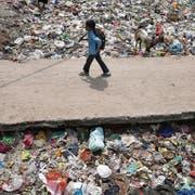 Spuren der Wegwerfgesellschaft: Ein Junge passiert auf seinem Schulweg in der indischen Hauptstadt Neu-Delhi eine Mülldeponie. (Rajat Gupta/AP, 22. April 2017)