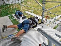 In luftiger Höhe auf schwingendem Untergrund montieren die Gerüstbauer, teils auf dem Bauch liegend, die Stahlträger und Alu-Beläge, die an den Abhängern (senkrechte Rohre) an der Energiebrücke hängen.