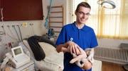 Hendrik Rogner posiert mit einem Beckenmodell für den Fotografen. Dieses zeigt, wie Kinder geboren werden. (Bild: Alex Spichale)