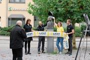 Der Fotograf und die vier Repräsentanten Branka Miljanovic, Marcel Koch, Sabine Keller und Samuel Schoeb (von links nach rechts) mit der eingehüllten Statue von Ulrich Bräker. (Bild: Flurina Lüchinger)