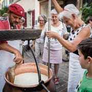 Käsermeister Werner Knöpfli beim Schow-Käsen vor dem Restaurant La Trouvaille. Wirtin Brigitte Bianchi hilft tatkräftig mit. (Bild: Reto Martin)