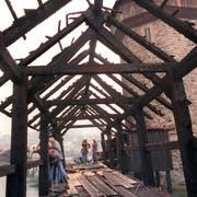 Feuerwehrleute verrichten Aufräumarbeiten nach dem Brand der Kapellbrücke in Luzern, aufgenommen am 19. August 1993. (KEYSTONE/Str)