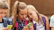 Alle haben ein Smartphone: Auch Kinder nutzen bereits Whatsapp. Bild: Getty