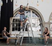 Das Dreierteam im OK des Kulturfestivals: Walter Boos (auf der Leiter), Lukas Hofstetter und Lina Samland beim Aufbau im historischen Innenhof. (Bild: Adriana Ortiz Cardozo)