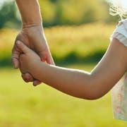 Eine Frau nimmt ihr Kind an die Hand. (Bild: Getty Images)