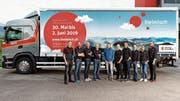 Das Iheimisch-OK mit seinem neuen, unübersehbaren Werbeträger im Hintergrund. In der Mitte Reto Zimmermann, dessen Firma als Co-Sponsor mitwirkt. (Bild: PD)
