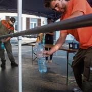 Zivilschützer füllen Flaschen für Anwohner ab, deren Trinkwasser verunreinigt wurde. (Bild: Samuel Golay/Ti-Press)