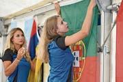 Zwei Spielerinnen des FC Weinfelden-Bürglen hängen die Fahnen der WM-Teilnehmer im Zelt beim Restaurant Frohsinn auf. (Bild: Mario Testa)