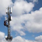 Ein Techniker rüstet eine Mobilfunkantenne mit 5G-Elementen aus. (Bild: KEYSTONE/Peter Klaunzer)