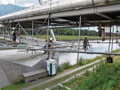 Gut gesichert arbeiten die Gerüstbauer auf der spaktakulären Baustelle. Sie montieren an der Energiebrücke Buchs–Schaan in luftiger Höhe ein Hängegerüst, damit danach die Fernwärmeleitungen an den Brückenboden gehängt werden können. (Bilder: Heini Schwendener)