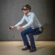 Physiotherapie als Mixed-Reality-Erfahrung: Matthias Heuberger, Leiter des CSS Health Lab, macht eine Kniebeuge, die ihm die virtuelle Therapeutin Alexa (weiter unten) vorzeigt. Bild: Pius Amrein (Luzern, 29. Oktober 2018)