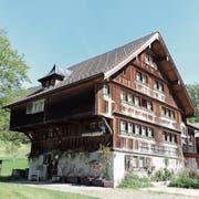 Ein typisches Toggenburger Haus mit weissem Sockel, seitlichen Überhängern, einer braungebrannten Fassade und Fensterwagen an der Hauptfassade. (Bild: PD)