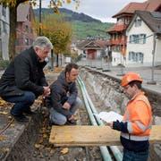 Gemeinderat Adolf Scherl, Patrik Dommen (Leiter Bauamt) und Bauleiter Roman Krummenacher (von links) begutachten die Dorfbach-Baustelle. (Bild: Corinne Glanzmann, Buochs, 5. November 2019)