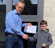 Der Drittklässler Loris Sedlmeyer erhält von Schulleiter Sebastian Schaad das Diplom des Känguru-Mathewettbewerbs. (Bild: PD)